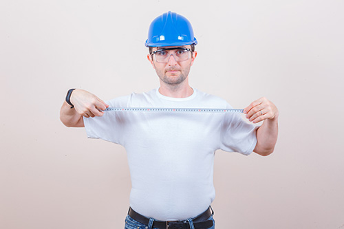 Construction worker holding measuring tape in t-shirt, jeans, he