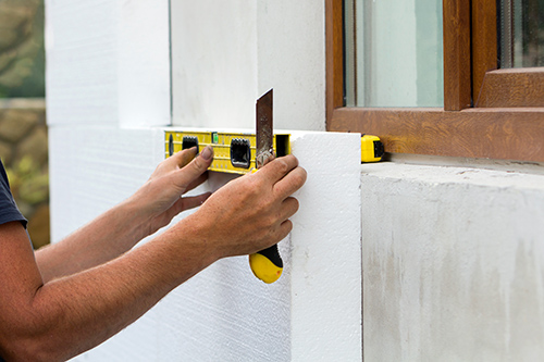 Construction worker insulating house wall with styrofoam insulat
