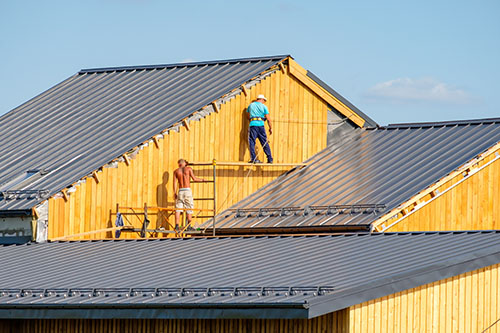 Workers are building the roof of a country house.